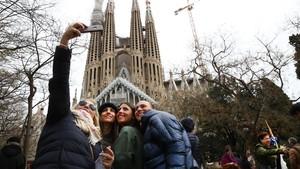 Una familia se fotografía al pie de la Sagrada Família.