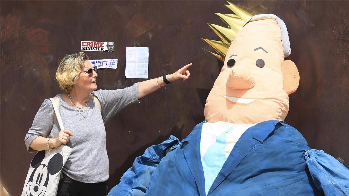 Una mujer señala a un muñeco de Benjamín Netanyahu en Tel Aviv (Israel).