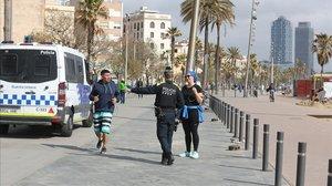 Un agente de la Guardia Urbana da el alto a una pareja de 'runners' en la Barceloneta.