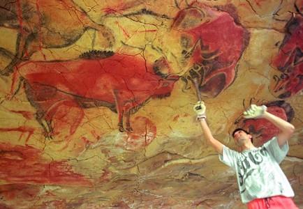 Un operario repara la reproducción de una de las pinturas de la cueva de Altamira