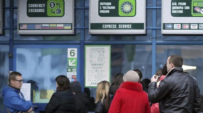 Bielorrusos hanec cola, este viernes, ante una oficina de cambio en Minsk.
