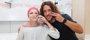 Carles Puyol y una paciente del Hospital de día posan con la cara pintada haciendo el gesto de la campaña del SJD Pediatric Cancer Center Barcelona.