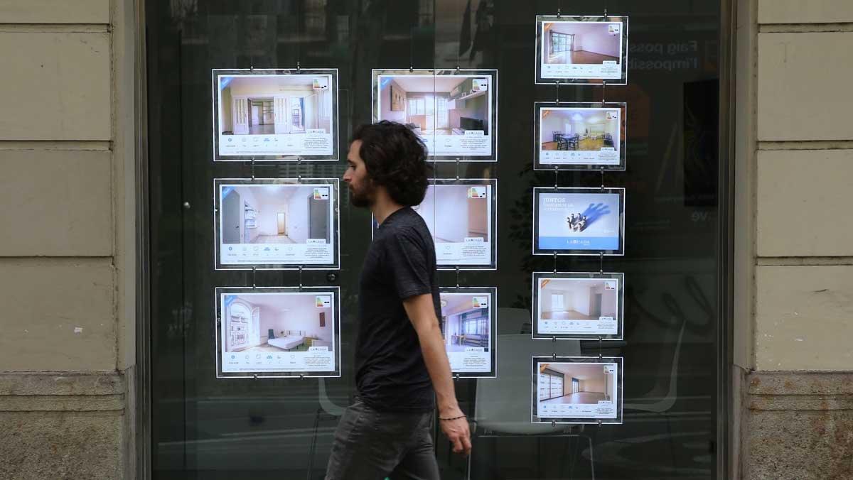 Un chico pasa por delante de una inmobiliaria.