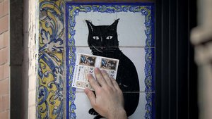 Un hombre pasa dos décimos de la Lotería de Navidad por el popular azulejo de la administración de loterías El Gato Negro en Sevilla.