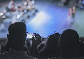 Un espectador haciendo una foto en plena función en el Teatre Grec, el pasado miércoles.