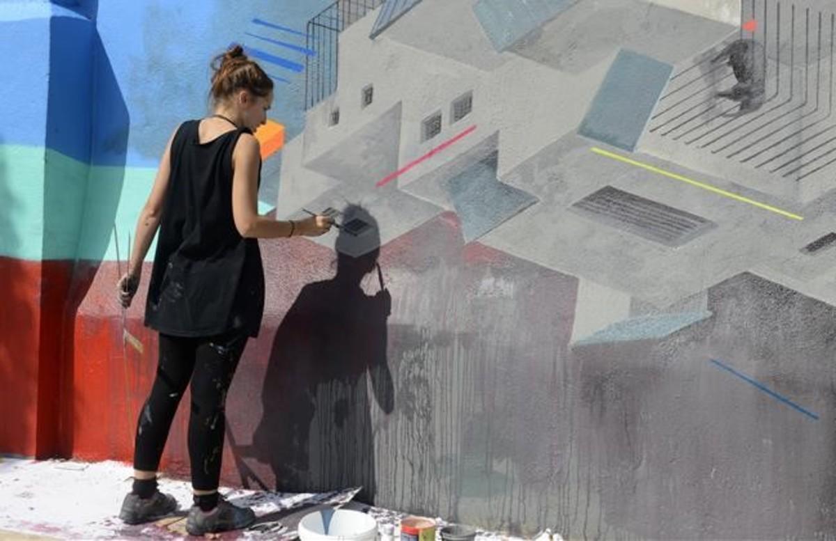 La artista Cinta Vidal pinta con pinceles una obra crítica con el zoo de Barcelona.