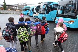 Un grupo de niños se dirige al autobús escolar en Monfero (A Coruña).