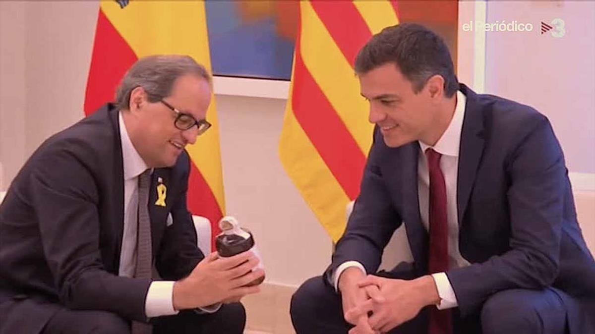 Quim Torra muestra la botella de ratafía aPedro Sánchez, el lunes en la Moncloa.