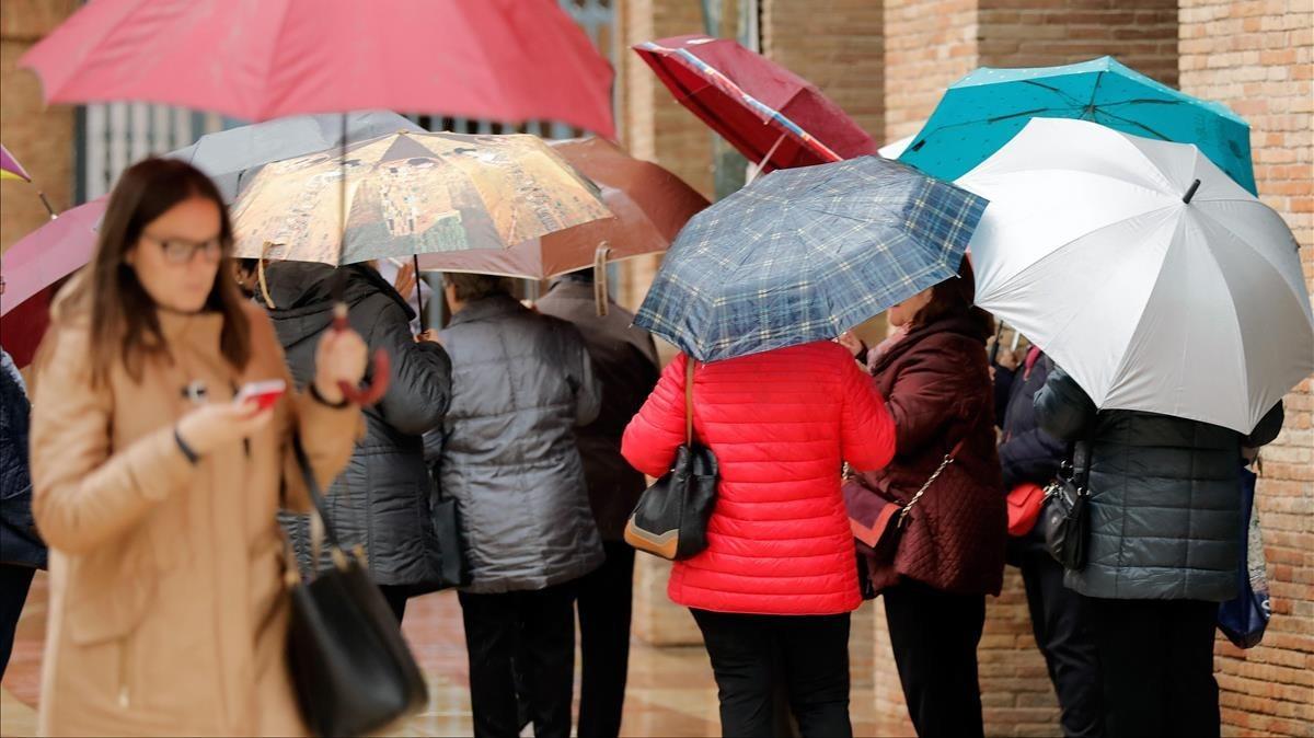Unas personas se protegen de la lluvia.