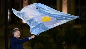 Macri ondea una bandera argentina en el mitin de clausura de su campaña electoral, en Córdoba.