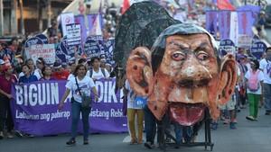 Manifestantes en Manila durante el Día Internacional de la Mujer empujando una efigie del presidente filipino, Rodrigo Duterte