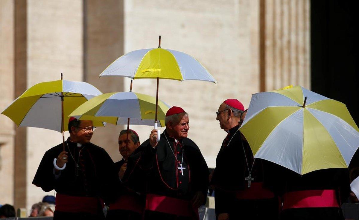 Miembros del clero se resguardan del sol con paraguas en la plaza de San Pedro, en El Vaticano.