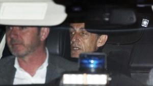 Nicolas Sarkozy abandona en el interior de un automovil la comisaría de policía enNanterre, a las afueras deParís, donde ha declarado.