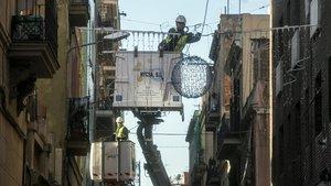 Un operario coloca unas luces de Navidad en una calle de Barcelona.