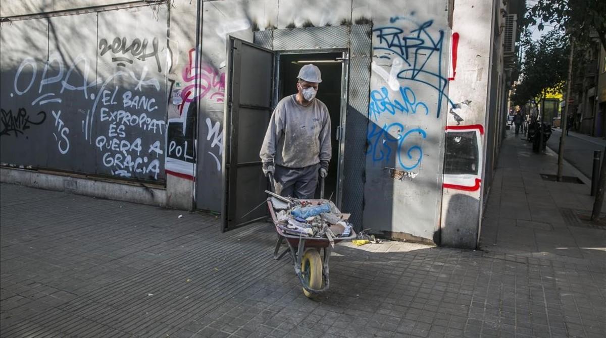 Un operario saca restos de las obras del local conocido como 'banco expropiado', en Gràcia.