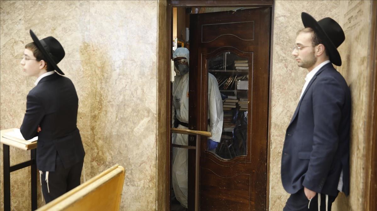 Un policia israelí protegido contra el coronavirus custodia a dos ultraortodoxos detenidospor haber acudido a rezar a una sinagoga.