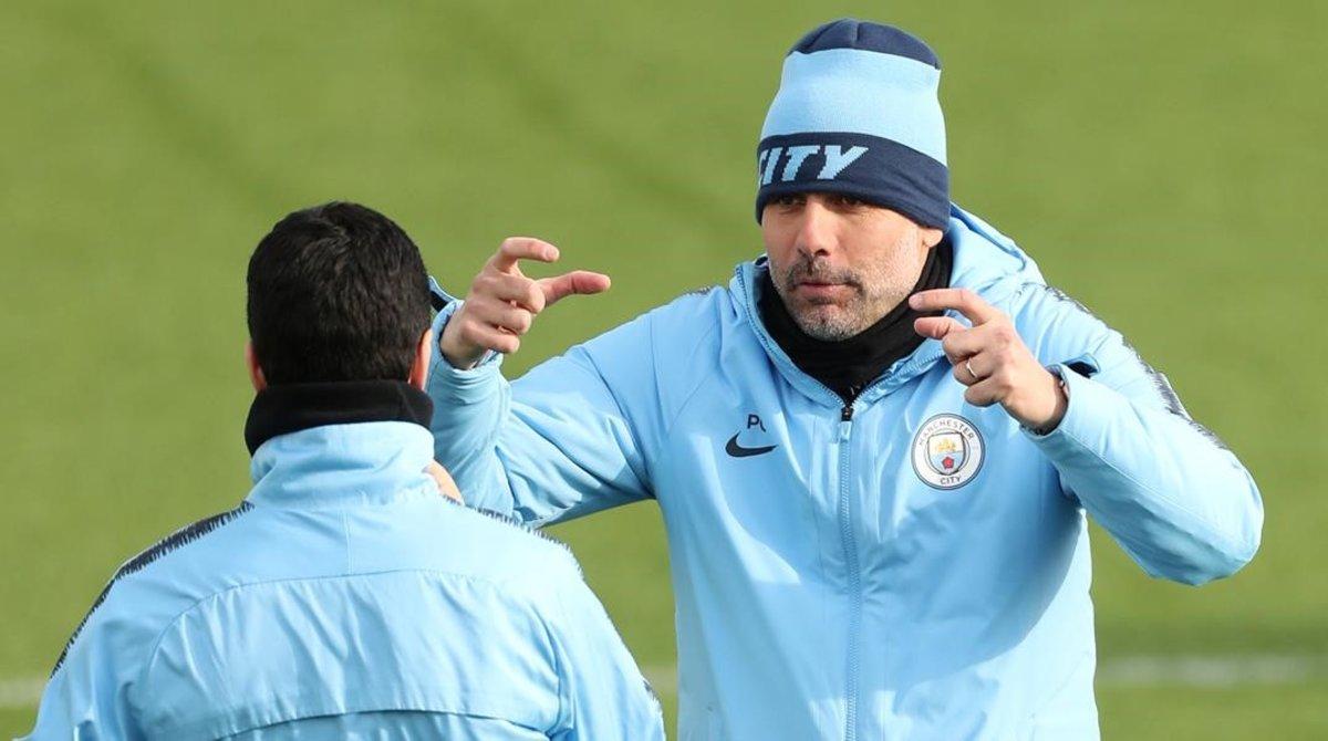 Pep Guardiola habla con Mikel Arteta, su ayudante, en el entrenamiento previo al City-Schalke