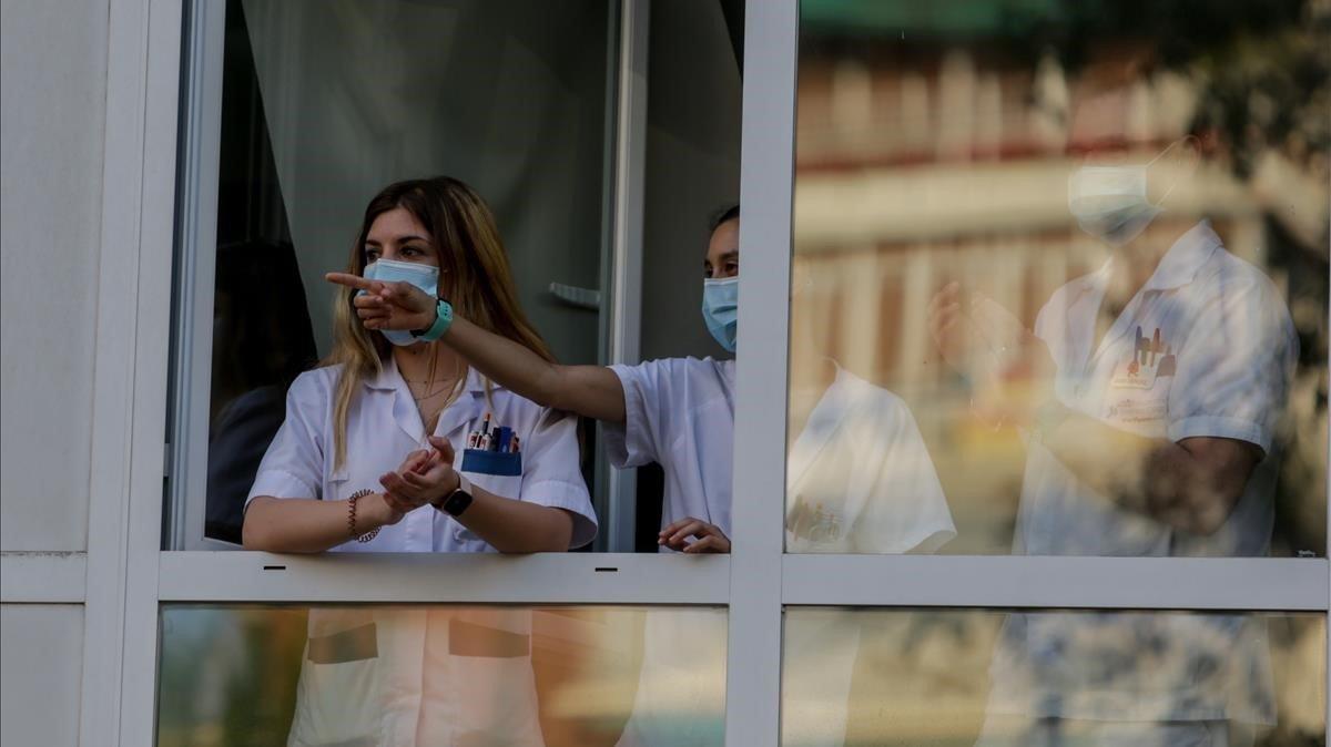 Personal sanitario del Hospital Fundación Jiménez Díaz de Madrid devuelve los aplausos durante el homenaje que le tributa la ciudadanía.