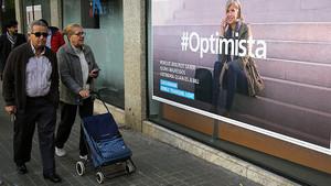 Varios viandantes, ante un anuncio de planes de pensiones de una entidad bancaria.