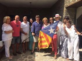 El president Puigdemont, con vestuario veraniego y sosteniendo una estelada, junto a Rahola, Laporta y otros amigos en Cadaqués.