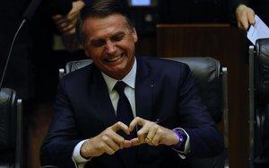 El presidente brasileño, Jair Bolsonaro, muestra un corazón con sus dedos durante su toma de posesión en el Parlamento.