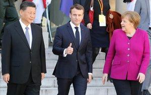 El presidente Emmanuel Macron (centro), flanqueado por la cancillera Angela Merkel (derecha) y el presidente chino Xi Jinping