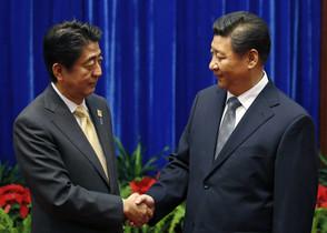 El primer ministro de Japón, Shinzo Abe (izquierda),y el presidente de China, Xi Jinping, se saludan en Pekín.