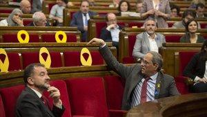 Quim Torra señala los escaños vacíos de los diputados suspendidos.