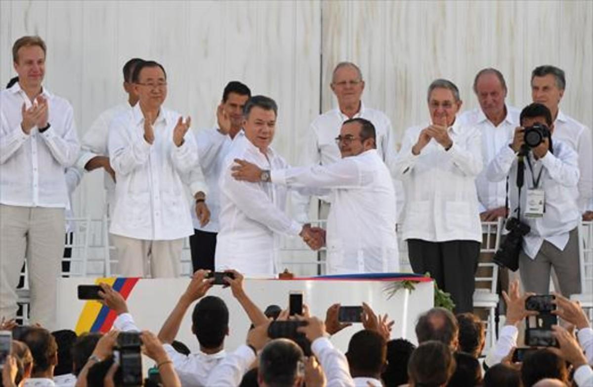 Santos y Timochenko se dan la mano entre los aplausos de Ki-mon, Castro y el rey emérito Juan Carlos, entre otras personalidades.
