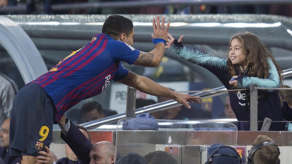 Suarez chocando su mano con sus hijos en la primera fila de la grada.