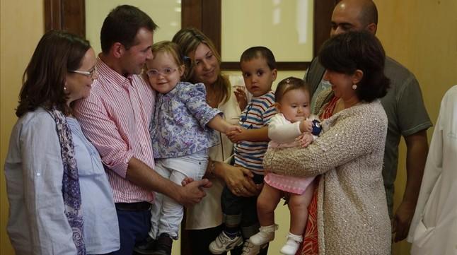 Tres niños operados en Vall d'Hebron de espina bífida con sus familiares.