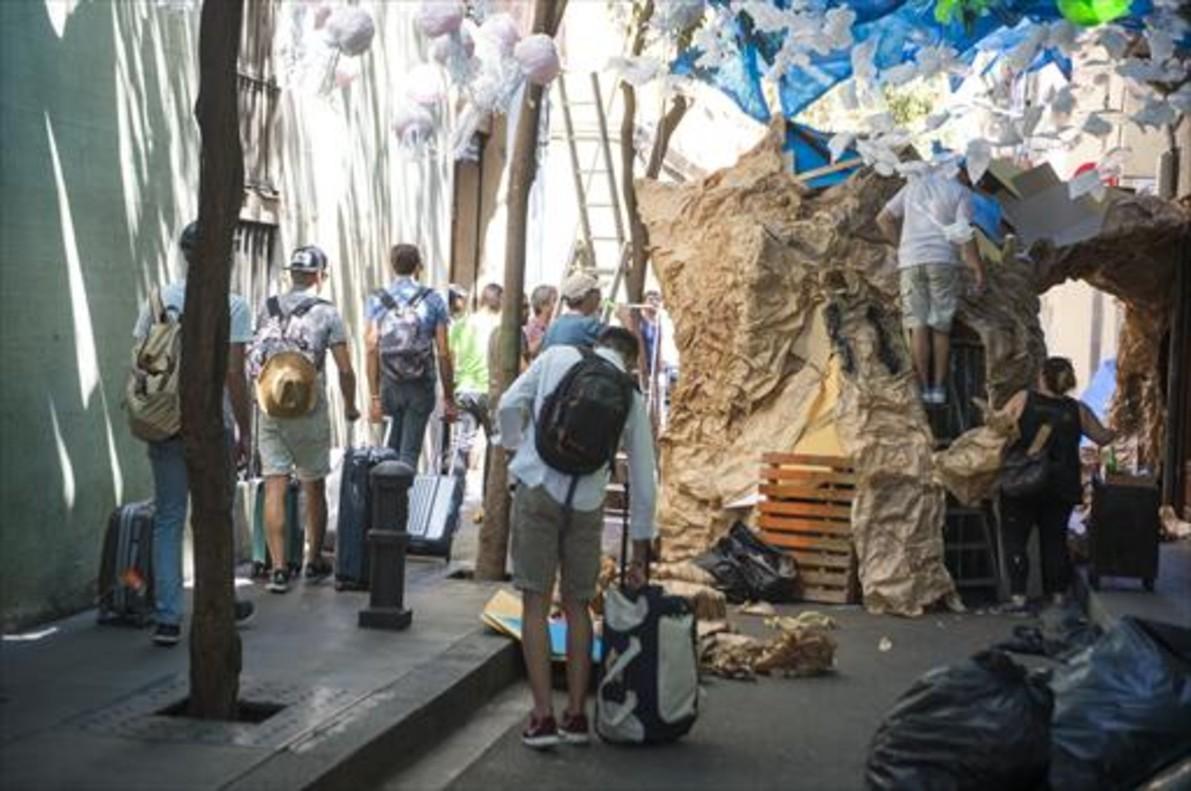 Turistas con su equipaje entre los vecinos engalanando una calle de Gràcia.