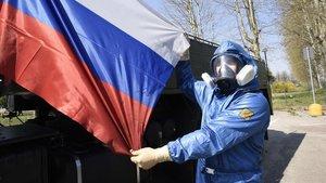 Una mujer muestra una bandera rusa durante una intervención en una residencia sanitaria en la que participaron soldados del Ejército ruso e italiano, el pasado 7 de abril en Treviglio.