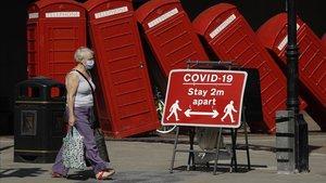 Una mujer pasa por un cartel en el que se exige a los londinenses que mantengan la distancia de seguridad, el 22 de junio pasado.