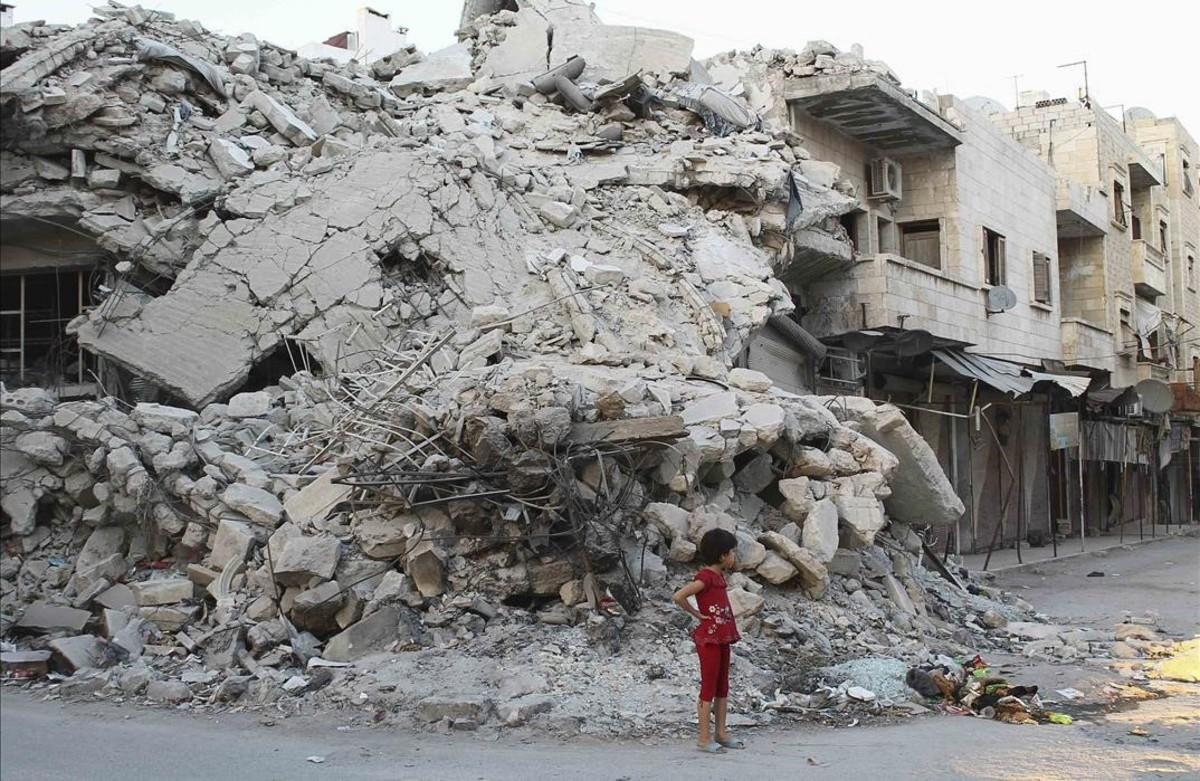 Una niña en frente de un edificio destruido por los aliados de Asad en la provincia de Idlib.