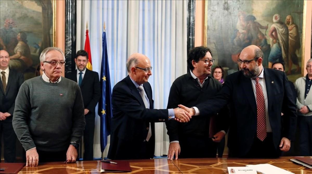 El ministro de Hacienda, Cristóbal Montoro, saluda al representante de CSIF, Miguel Borra, en presencia de los de CCOO, Francisco Fernández (a la derecha del ministro) y UGT, Julio Lacuerda (a su izquierda).