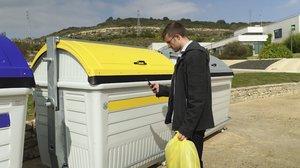 Un usuario utiliza su móvil para identificarse en un contenedor inteligente.