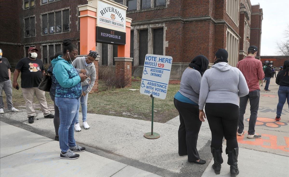 Votantes hacen cola en los alrededores de la Universidad Riverside, en el marco de las elecciones primarias presidenciales celebradas en medio del brote del covid-19, en Milwaukee, Wisconsin.