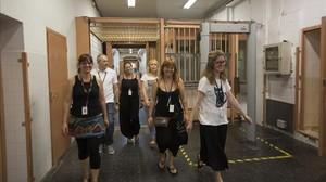 Anna Barrionuevo, Bàrbara Sentinella e Isabel Paredes (de izquierda a derecha, en primer término) y Xavier Aranda, Belén Celaya y Dolors Torner (detrás) caminan por los pasillos de la Modelo, este jueves.