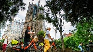 Dos de los pocos turistas que estos días visitan la ciudad paseando, este martes, en bicicleta frente a la Sagrada Família.