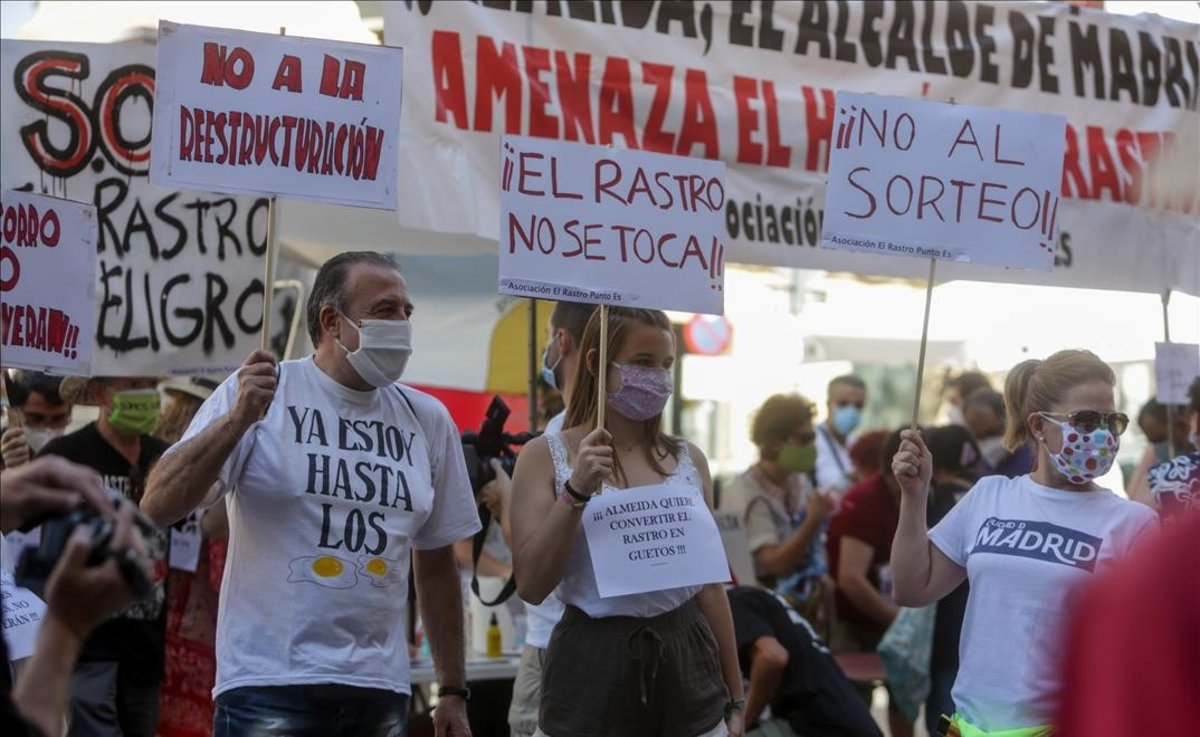 Comerciantes de El Rastro madrileño sostienen pancartas durante la manifestación en la Plaza del Cascorro para exigir sus puestos habituales y recuperar el modelo histórico del mercadillo.