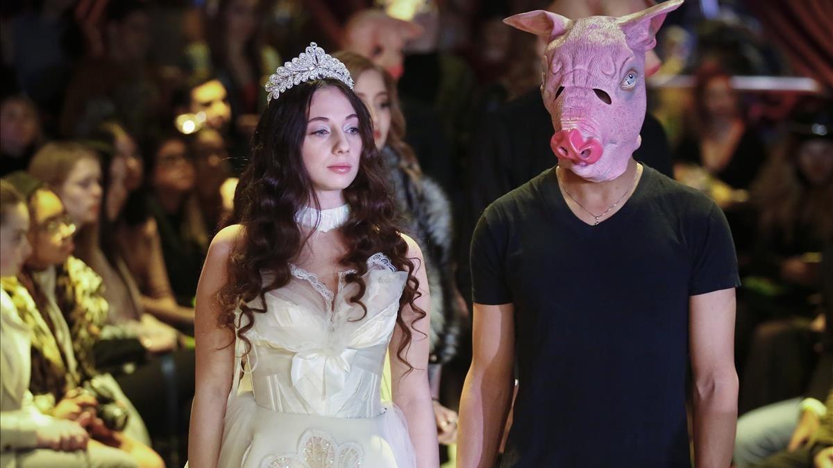 Sabrina Piper, esposada a un modelo con una careta de cerdo.