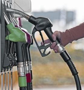 Un cliente coge la manguera de un surtidor en una gasolinera belga.