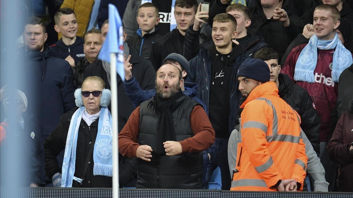 Un aficionado del Manchester City hace gestos racistas a los jugadores del United.