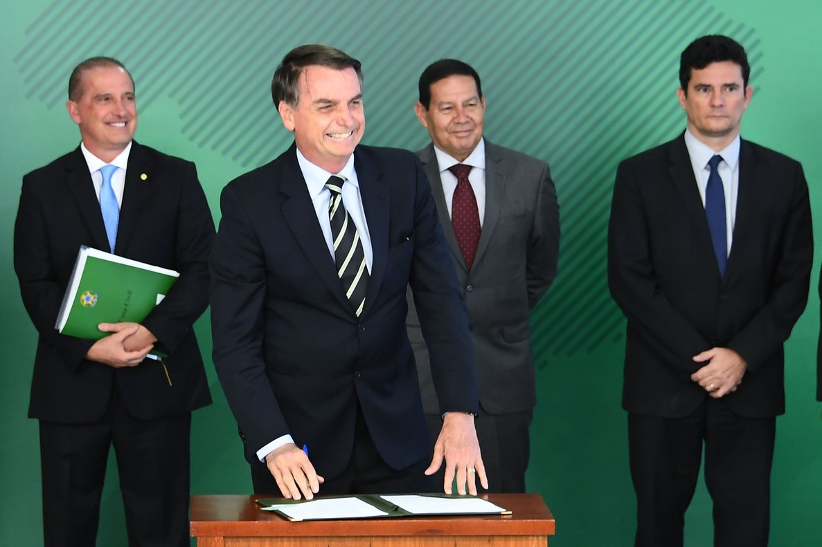 Brazilian President Jair Bolsonaro accompanied by Chief of Staff Onyx Lorenzoni  Vice-President Hamilton Mourao  2 and Justice Minister Sergio Moro  smiles as he signs a presidential decree that flexibilizes the possession of firearms  at Planalto Palace in Brasilia  Photo by EVARISTO SA   AFP