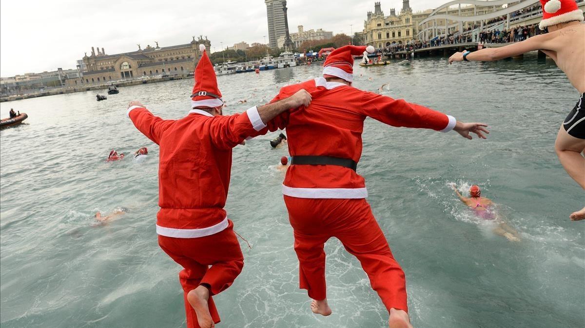 Dos nadadores se tiran al agua vestidos de Papa Noel durante la celebración de la Copa Nadal, en el Port Vell.