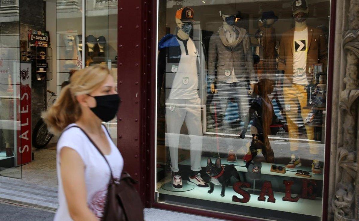 Una mujer con mascarilla pasea por el centro de Barcelona.