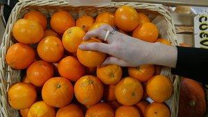 Una persona coge una naranja en un supermercado