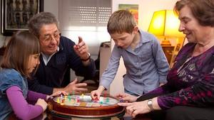 Dos abuelos juegan con sus nietos.