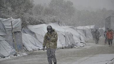 Diversos refugiats caminen sota la neu, al campament de refugiats de Moria, a l'illa de Lesbos (Grècia).